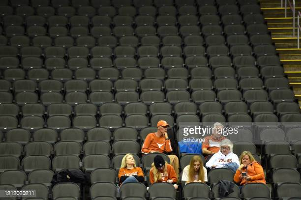 A small group of Texas fans sit in an empty Sprint Center prior to the announcement that the Big 12 basketball tournament would be cancelled due to...