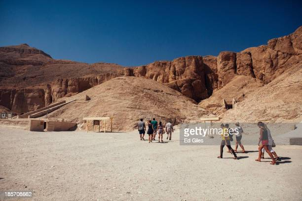 A small group of tourists walk toward the entrance to a tomb in The Valley of the Kings on October 23 2013 in Luxor Egypt The Valley of the Kings...