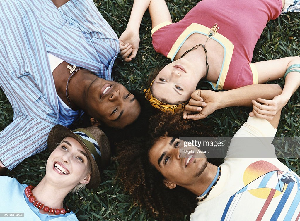 Small Group of Twentysomething Men and Women Lying Together on Grass : Stock Photo