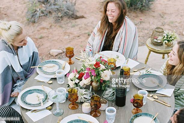A small group of women enjoying an outdoor meal in a desert.