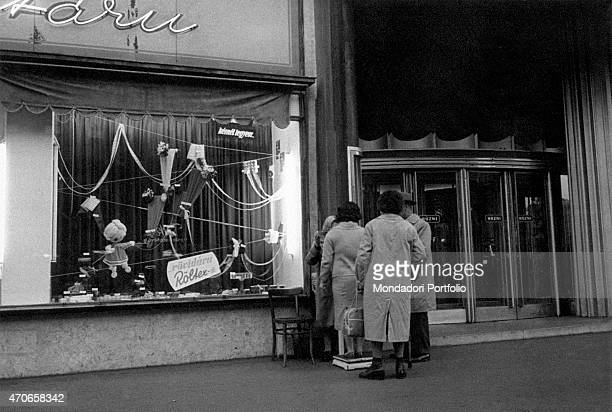 'A small group of women queues in front of a scale out of a shop at the exit of the biggest hotels of the city the often are women who invite the...
