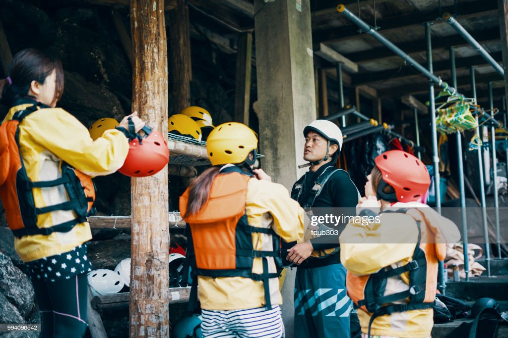 Small group of women trying on helmets in preparation for white water river rafting : Stock Photo