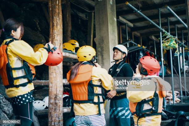 Small group of women trying on helmets in preparation for white water river rafting