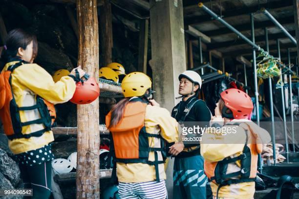 Kleine groep van vrouwen die proberen op helmen in voorbereiding voor het white water riverrafting