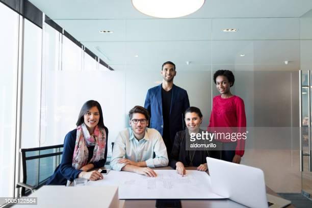 petit groupe de jeunes architectes, souriant à la caméra - plan moyen angle de prise de vue photos et images de collection