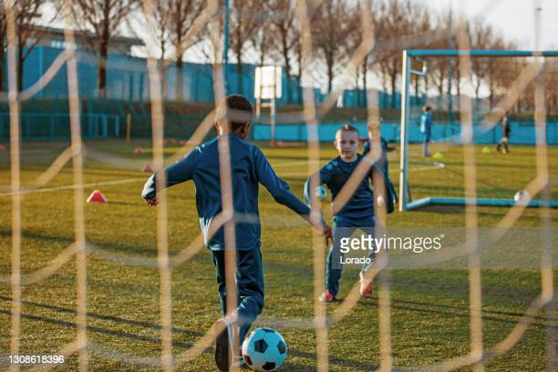 a small group of young boys and their coach training on the football pitch - practicing stock pictures, royalty-free photos & images