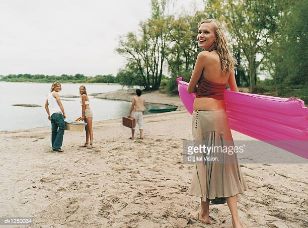 Small Group of Young People Arriving at a Beach at the Edge of a Lake Carrying a Lilo and a Picnic Hamper