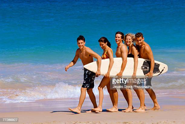 Small group of young people carrying a surfboard