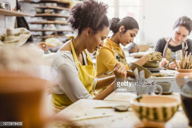 small group of young people creating pottery - hobbies stock pictures, royalty-free photos & images