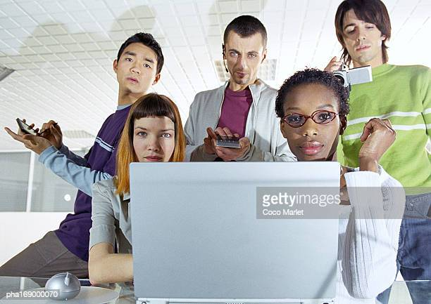Small group of young people, in focus, behind computer screen in foreground