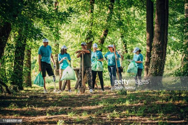 small group of young volunteers in the forest - ecologist stock pictures, royalty-free photos & images