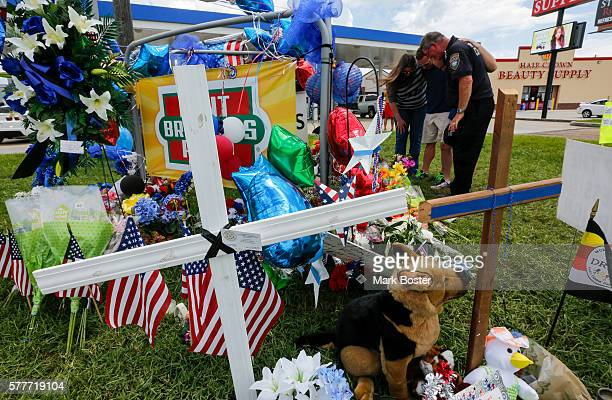 A small group prays together in a circle in front of the roadside memorial for the three slain police officers on Airline Highway in Baton Rouge July...