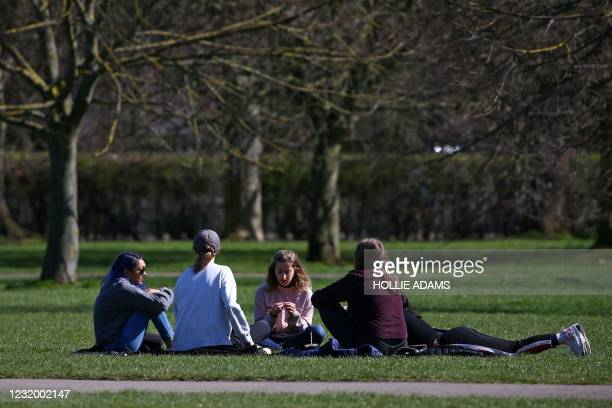 Small group sit and chat together in the warm weather in Regent's Park in London on March 29 as England's third Covid-19 lockdown restrictions ease,...