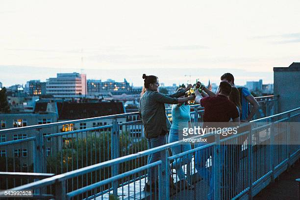 Gruppe der jungen Erwachsenen am Pool auf dem Dach, der reden und rösten Bier, skyline