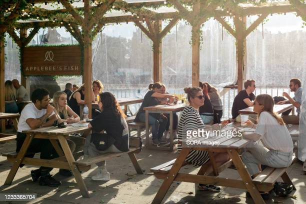 Small groups of people sitting with tables placed at safe distances at a pub in Waterloo, London. As the UK government lifted the restrictions...