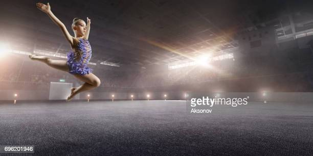 Une fille de petite gymnaste fait un saut sur une grande scène professionnelle