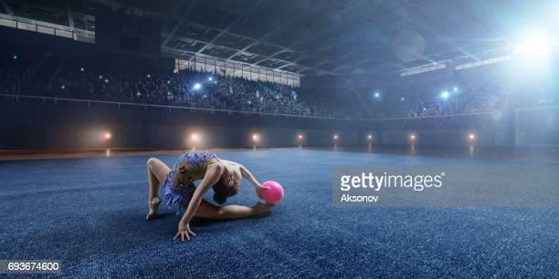 Une fille de petite gymnaste fait performance avec ballon de gymnastique sur une grande scène professionnelle