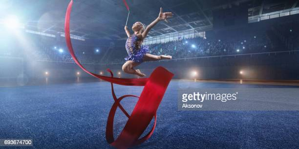 A small gymnast girl makes performance with gymnastic band on a large professional stage