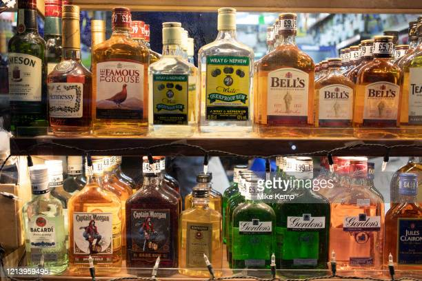 Small half and quarter bottles of spirits for sale in a corner shop window on 24th February 2020 in London, United Kingdom. Spirits are distilled...