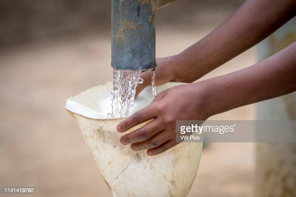 Small hands hold a funnel so that a water jug can be filled from a pump in Ganta, Liberia.