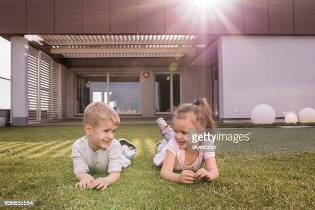 small happy kids relaxing in the backyard and communicating. - penthouse girls stock pictures, royalty-free photos & images