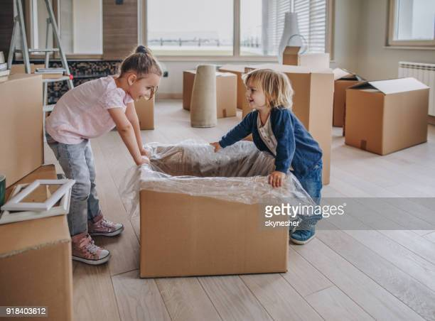 small happy siblings having fun while unpacking their belongings from carton box. - penthouse girl stock photos and pictures