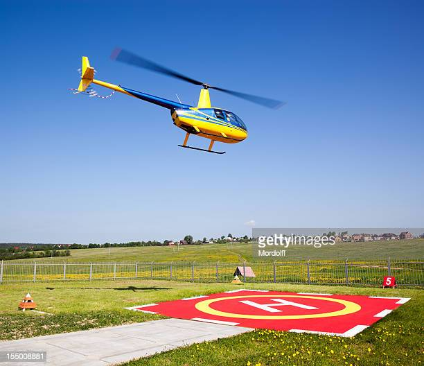 small helicopter taking off from heliport - helipad stock photos and pictures
