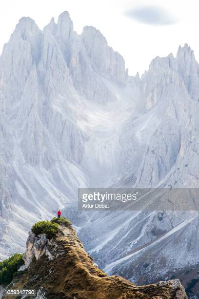 small hiker facing the sharp dolomite mountains in the italian alps. - erodiert stock-fotos und bilder