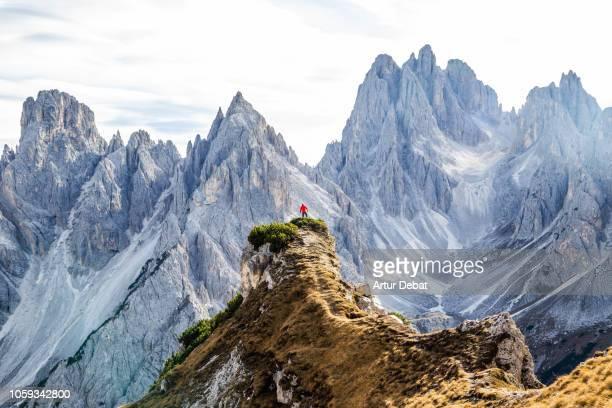 small hiker facing the sharp dolomite mountains in the italian alps. - トレチーメディラバレード ストックフォトと画像