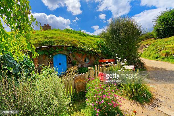 Small hobbit-hole with blue door and picket fence at Hobbiton film set in Matamata, New Zealand, on partly cloudy summer afternoon.