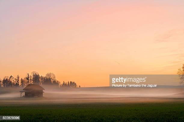 Small house and foggy sunset