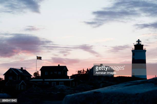 Small houses and lighthouse by sea at sunset