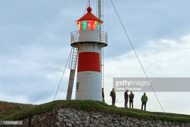 a small illuminated lighhouse on a hill and silhouettes of some people standein beside the light - rainer grosskopf stock pictures, royalty-free photos & images