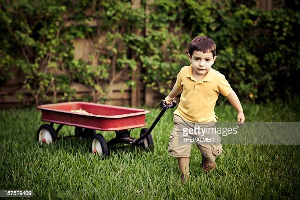 small kid pulling a red wagon - toy wagon stock photos and pictures