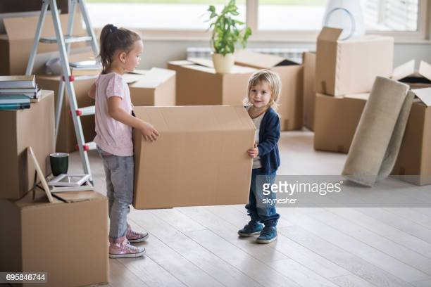 Small kids cooperating while carrying cardboard box in new apartment.
