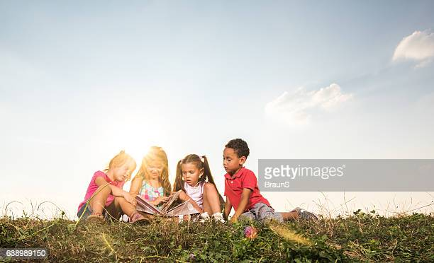 Small kids looking at picture book in nature.