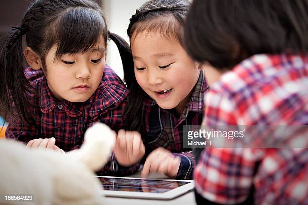 Small kids playing with a digital tablet.