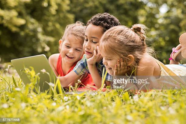 Small kids relaxing in grass and using laptop.