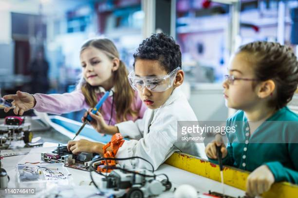 Small kids working on computer components in laboratory.