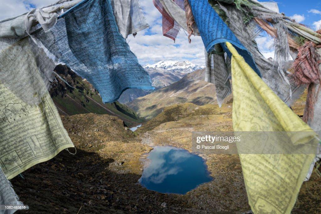 Small lake and prayer flags from Keche La pass, Gasa District, Snowman Trek, Bhutan : Stock Photo