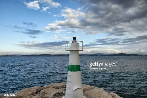 small lighthouse at marina entrance,aegean turkey. - emreturanphoto stock pictures, royalty-free photos & images