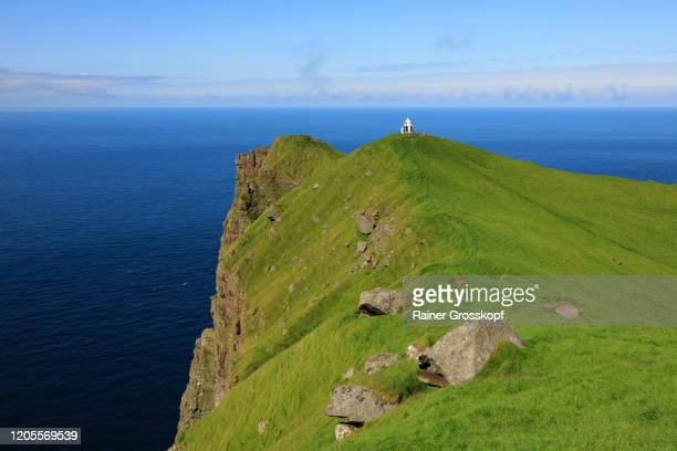 a small lighthouse on top of a grassy steep cliff high above the sea - rainer grosskopf stock-fotos und bilder