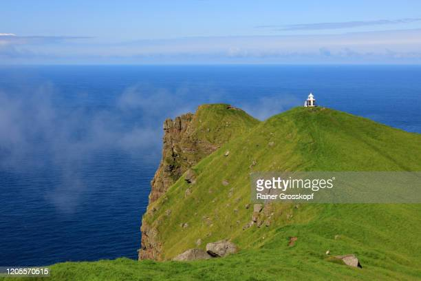 a small lighthouse on top of a grassy steep cliff high above the sea - rainer grosskopf fotografías e imágenes de stock