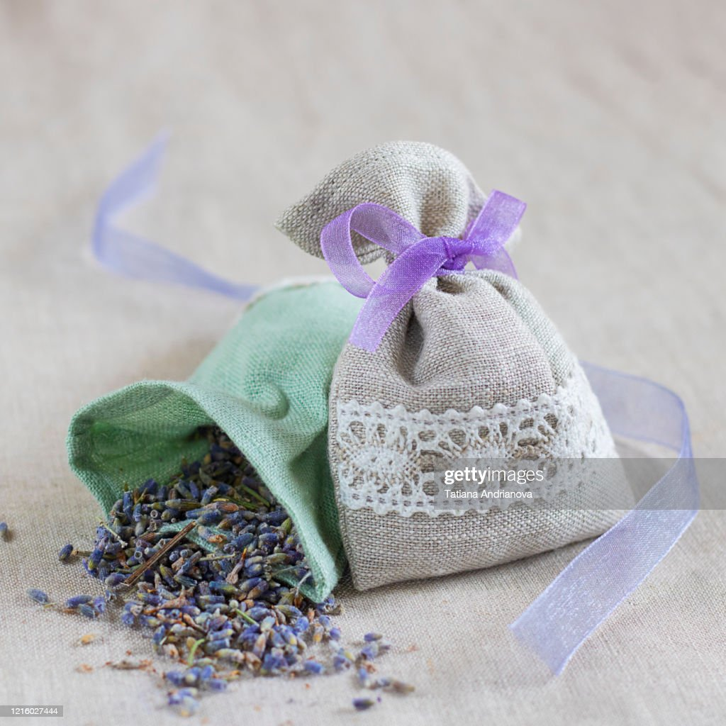 Small linen sack filled with dried lavender decorated with lacework and violet ribbon coque, two sachets, one is opened. Composition on the natural flaxen background. Square : Stock Photo