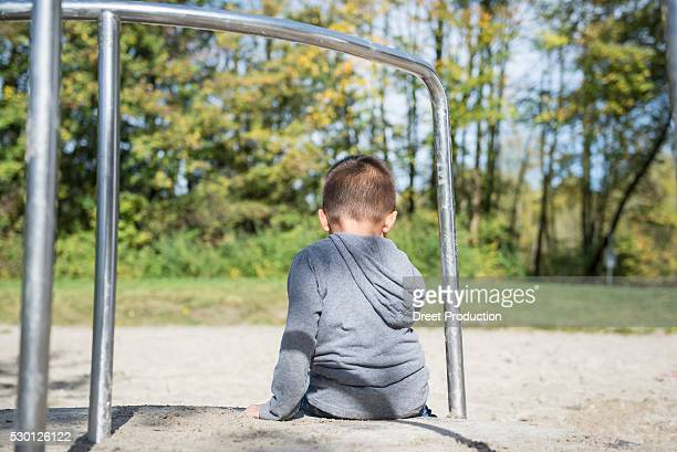small lonely boy sitting alone in playground - spaß stock pictures, royalty-free photos & images