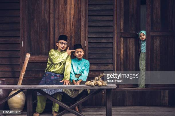 a small malay family in malay traditional showing their  happy reaction during hari raya celebration. - shaifulzamri imagens e fotografias de stock