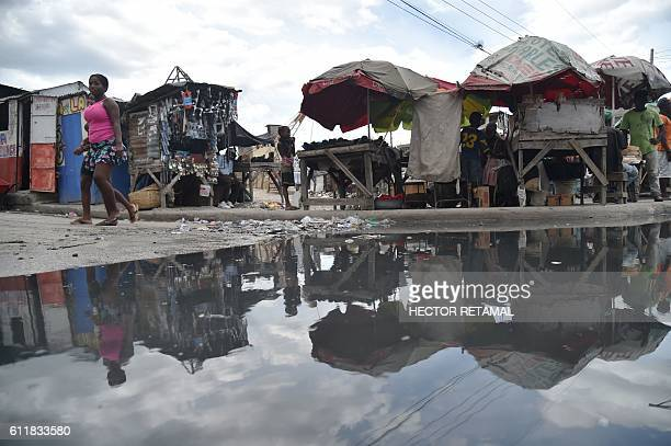 A small market is reflected in a puddle near the canal of Portail Leogane in the Haitian capital PortauPrince on October 1 2016 As Hurricane Matthew...