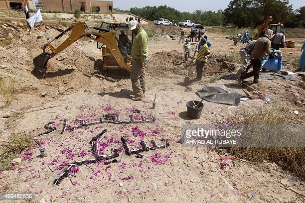 A small memorial reading in Arabic the martyrs of Speicher is seen as members of the Iraqi security forces inspect a mass grave containing the...