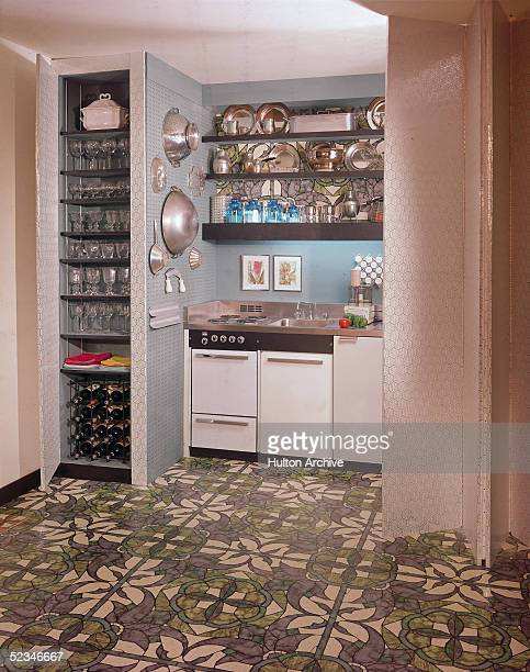 A small model kitchen features a stove an oven a sink shelves of pots and pans a Cusinart food processor and a closet cabinet of shelves of glasses...