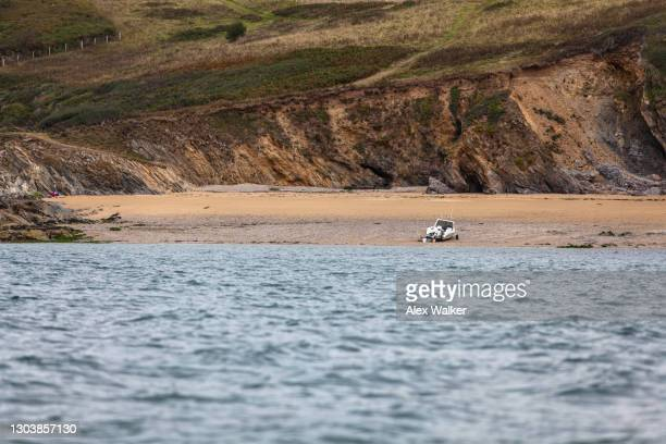 small motor boat beached on an isolated quiet beach - falmouth england stock pictures, royalty-free photos & images
